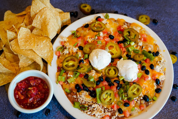 large plate of nachos with scattered tortilla chips and salsa